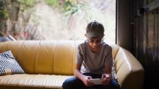 Boy sitting on sofa near window texting on mobile phone