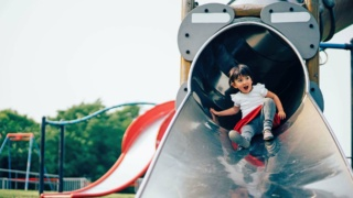 Toddler girl going down a playground slide