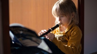 Child (6-7) sitting in a doorway at home, practising playing the recorder