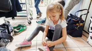 Young girl tying her shoes whilst sitting on the floor