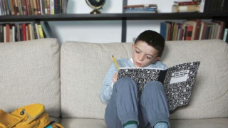 Boy with Noonan Syndrome doing schoolwork on a sofa