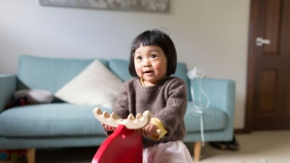 Young girl play riding wooden reindeer