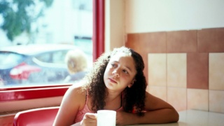 Teenage girl in a café with a cup of tea
